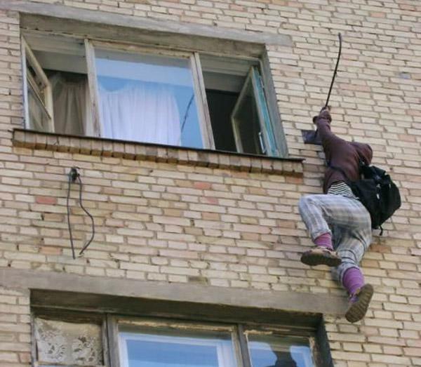 Человек висит за окном